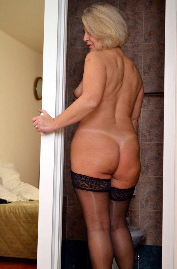 Une femme cougar pose nue chez elle